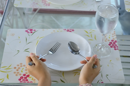 hands hold spoon fork with empty plate and wine glass of water on the beautiful mat photo