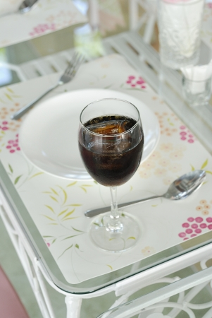 Cola into a wine glass with ice cubes with a dish spoon and fork on the table  photo