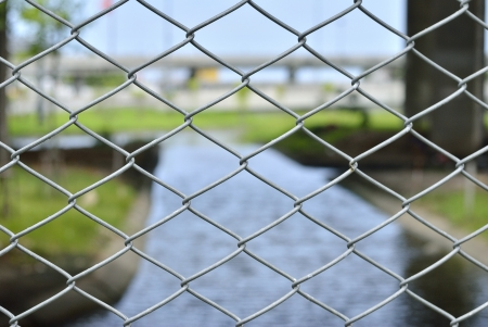 wire mesh with river background - A shiny chrome grill - chain link fence - steel wire mesh texture - wired fence photo
