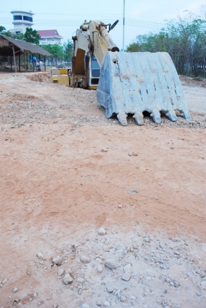 loader machine during earth moving works outdoors at construction site in the large hole photo