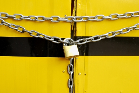 metal chain and lock on yellow background - Key lock locked with a chain - photo