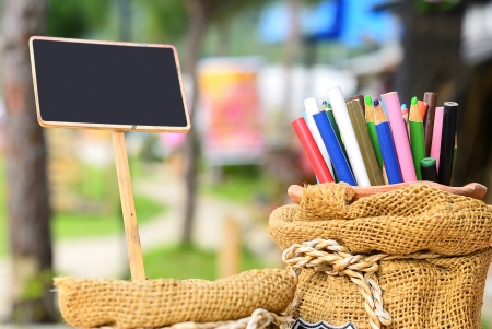 Colored pencils in sack bag with clean small blackboard by chalk on the nature background,Place your text photo