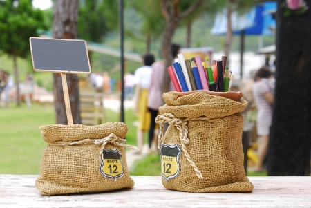 Colored pencils in sack bag with clean small blackboard by chalk on the nature background,Place your text Stock Photo - 15196886