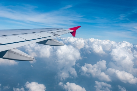 Wing of the plane on sky background - plane wing with cloud patterns - view from the window of a plane of the wing, the sky - View of jet plane wing Stock Photo - 17073319