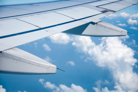 Wing of the plane on sky background - plane wing with cloud patterns - view from the window of a plane of the wing, the sky - View of jet plane wing Stock Photo - 17073350