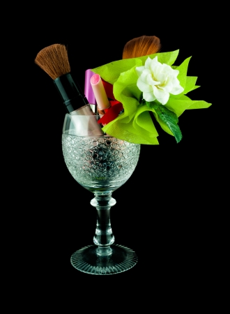 Wine crystal glass with brushes and makeup cosmetics isolated on black - set of cosmetics in crystal glass Stock Photo