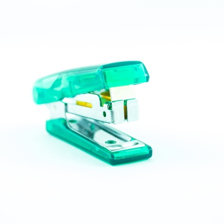 Green transparent stapler isolated on a white background photo