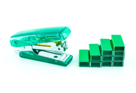 isolates: Green stapler and bunch of staples isolated on white