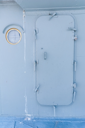Battleship door with steel porthole of ship photo