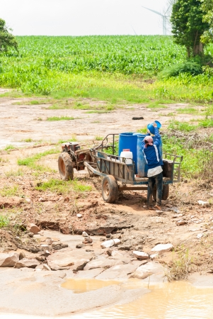 A man carry a pail water to the old truck in the nature field photo