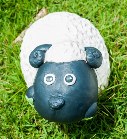 Smile white sheep statue in green grass on daytime photo