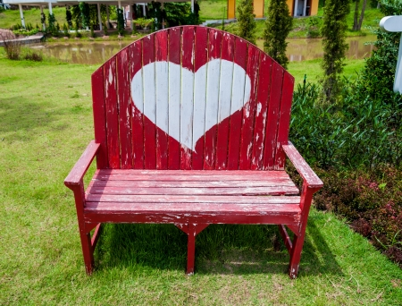 Red bench chair with heart symbol in the garden or park photo