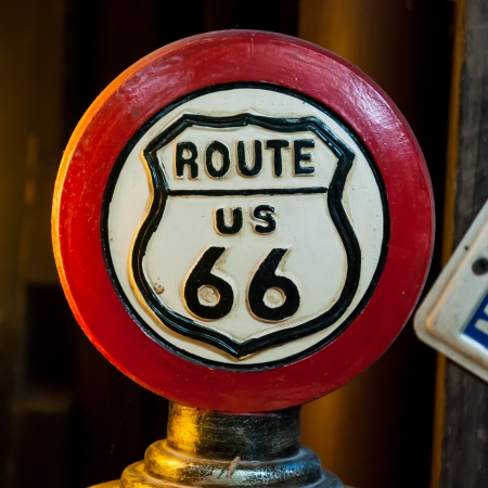 Red Circular of Route 66 Sign (orange light from left side) photo
