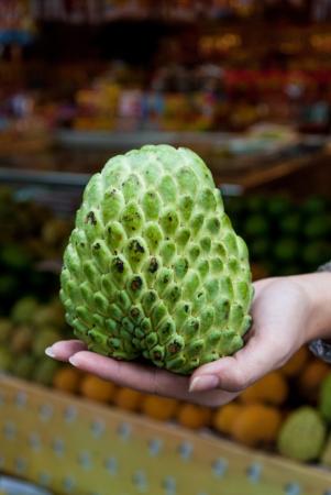 chirimoya: Sugar or custard apple in hand on fruit market background