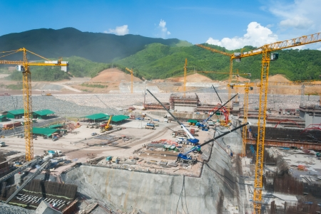 Huge construction site for dam with cranes in mountain area photo