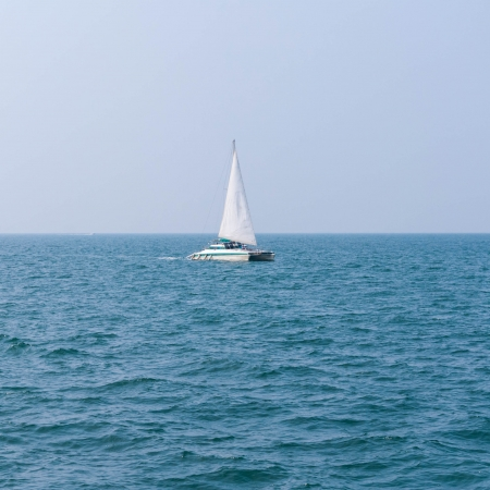 Sailing boat on the clear sea - Small yatch floating photo