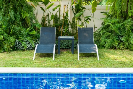 accomodation: View of black long chairs set aside swimming-pool Stock Photo