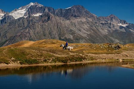 A rider on a horse near the lakes of Coruldi spodnozhaya mountains. Ushba. Upper Svaneti, Mestia, Georgia. High Caucasian ridge.