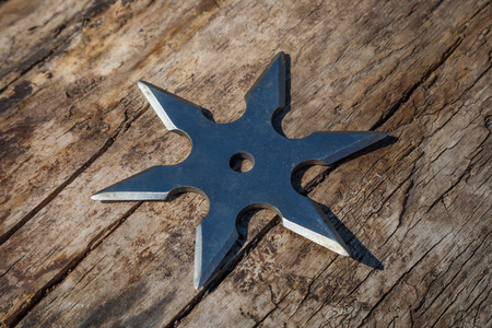 Shuriken (throwing star), traditional japanese ninja cold weapon stuck in wooden background