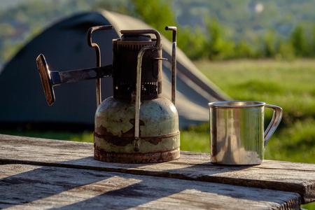 An old Soviet kerosene primus  and a steel mug on nature.