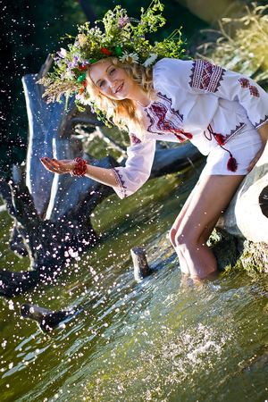 Beautiful  girl in national Ukrainian embroidery shirt and wreath of wild flowers. Holiday of Ivan Kupala in Ukraine.