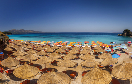 Beautiful beach with umbrellas for a holiday in Albania. Ionian Sea 에디토리얼