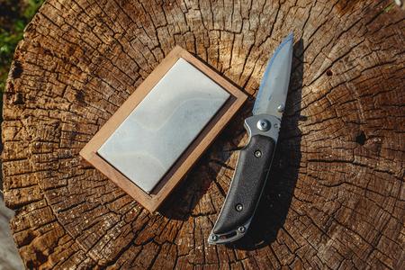 나무 배경에 날카로운 칼과 숫돌 스톡 콘텐츠 - 107255644