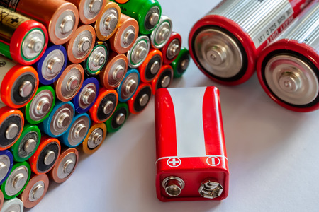 Closeup of pile of used alkaline batteries. Several in rows.