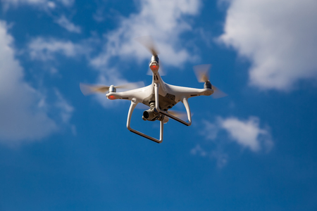 Quadcopter in flight against a blue sky. Drone Stock fotó