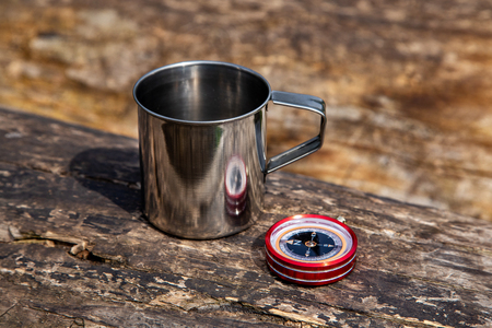 Tourist steel cup and compass in the summer forest Reklamní fotografie