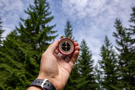 Compass in the hands in the Carpathian forest. Traveling in the mountains.  스톡 콘텐츠