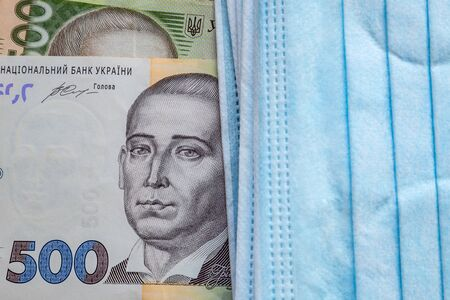 Money notes of Ukraine and a protective mask from a virus. World economic crisis associated with coronovirus.