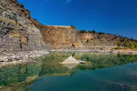 Abandoned granite and sand quarry with a lake. Stone extraction in the canyon.