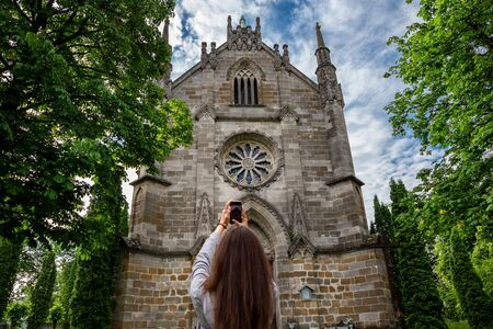 Beautiful girl with a phone on the background of the Gothic church. Tourism in Europe