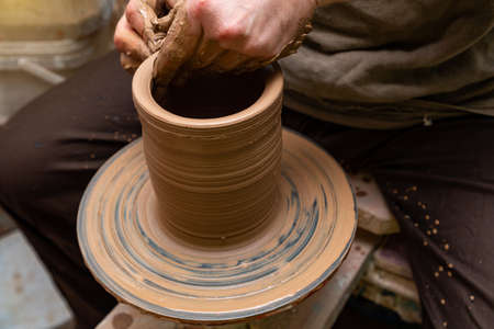 Creating a pot of clay close-up. Hands making products from clay. Potter at work. Stock Photo