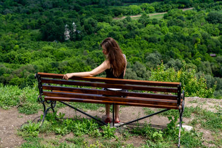 Girl and a beautiful view with a bench on the canyon.