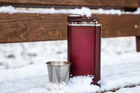 Steel alcohol flask in the winter forest. men's accessory for alcohol.