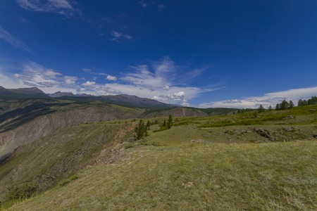 Mountain valley. Blue sky and white clouds. Summer sunny day. Фото со стока