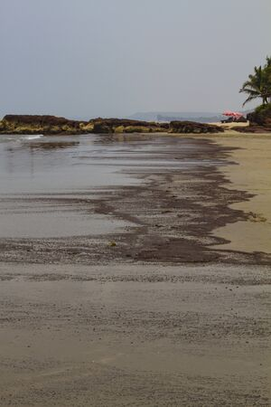 Pieces of oil products washed up on the seashore after crash tanker in India, GOA. Ecology problem concept.