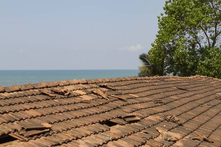 Broken old terracotta tile on a roof on sea background. Traditional cover in India, GOA. Summer time.