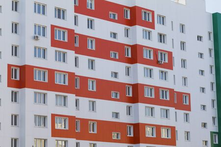 The facade of a new modern multi-storey residential building in Russia. White-orange painted. Close up.
