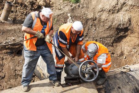 dismantling:  Three locksmith produce dismantling steel valves.    Editorial