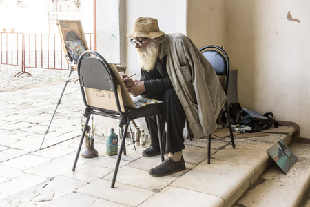 passerby: New Athos, Abkhazia - 14 Oct. 2015: draw pictures on novoivankovo artist for supervision in the history of the monastery.