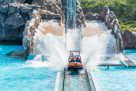 Zhuhai, Guangdong, China- October 15, 2016: People sitting on boat doing extreme sport water slide with splash on the track in park of Chimelong Ocean Kingdom, Zhuhai, China