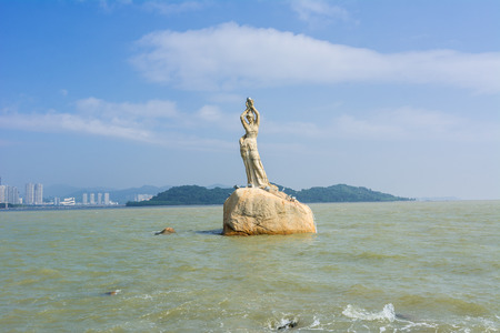 Zhuhai, Guangdong, China- October 16, 2016: Landmark of Zhuhai city of China. Statue of Fish Woman, fisher girl stature with background of sea, island, and tall buildings