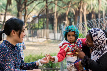 Hyderabad City, Andhra Pradesh, India- November 18, 2016:  A smiling Chinese woman tourist shaking hand with Indian Muslim kid and his mother Editorial
