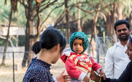 Hyderabad City, Andhra Pradesh, India- November 18, 2016: Editorial: A smiling Chinese woman tourist interact with Indian Muslim kid and his mother