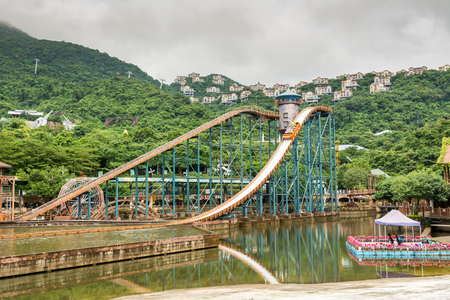 Shenzhen, Guangdong, China- September 16, 2016: Editorial: People sitting on boat doing extreme sport water slide with splash on the track in park of Overseas Chinese Town East