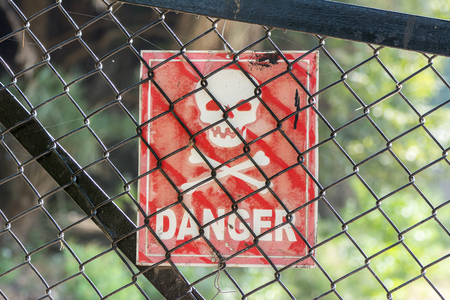 Sign of danger hanging behind wire netting fence