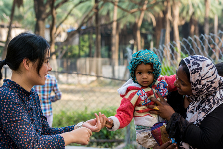 Hyderabad City, Andhra Pradesh, India- November 18, 2016: A Chinese tourist shaking hands with an Indian Muslim kid and his mother